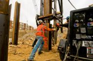 Pile driving crew placing a piling section for welding before driving further into the earth.