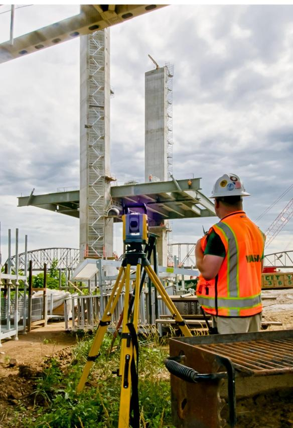 William Moylan talks with his partner Garren Wesseman as they measure the placement of the side girder and road girders of the downtown span.