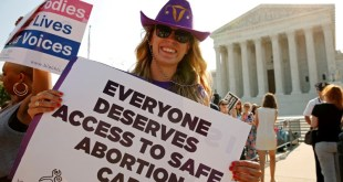 """A demonstrator wearing a cowboy hat with a uterus symbol holds a sign outside the U.S. Supreme Court as the court is set to rule on a legal challenge by abortion providers to a Texas law requiring doctors performing the procedure to have """"admitting privileges"""" at local hospitals and clinics to meet hospital-grade standards in Washington, U.S. June 27, 2016. REUTERS/Kevin Lamarque"""