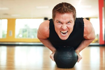 athletic man does pushups with medicine ball