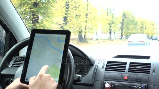 Tablet with map gps navigation for direction  location  Man driver in  modern car looking for directions in the map  Man is driving car in rainy   cloudy day  Rain  Business Tablet with map gps navigation for direction  location  Man driver in  modern car looking for directions