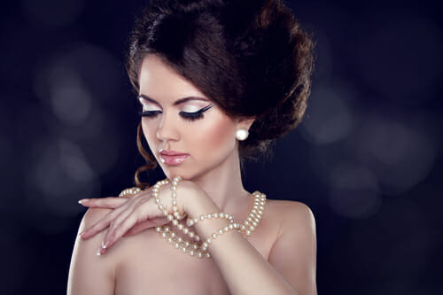 Glamour portrait of beautiful woman with pearl necklace on the bared shoulders
