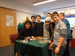Foto von Frau Rahlens beim Signieren mit Schülern der PUS
