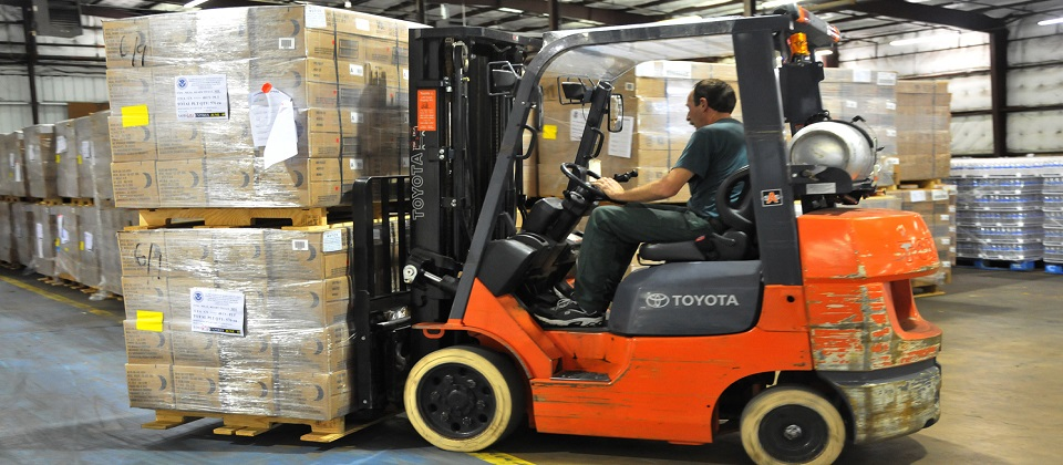 Tyler, TX September 2,2008-- A member of the Texas Forest Service moves a batch of MRE (meals ready to eat) in a warehouse in Tyler, TX.supplies in a  The warehouse is being used to handle basic supplies of water and MRE (meals ready to eat) for distribution to residents affected by Hurricane Gustav.  Photo by Patsy Lynch/FEMA
