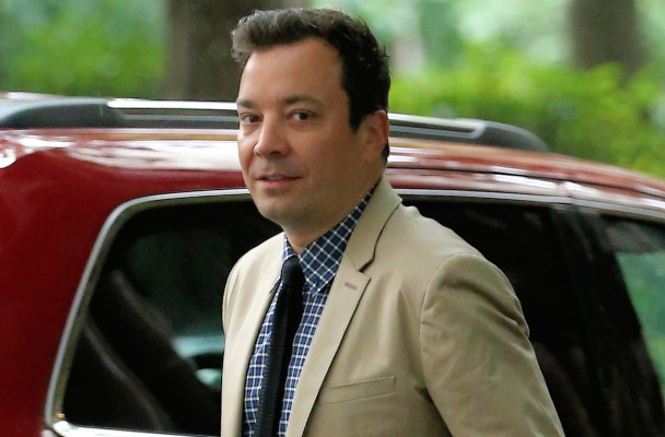 Comedian Jimmy Fallon heads to work with his left hand in a cast and blue suede shoes untied in New York City