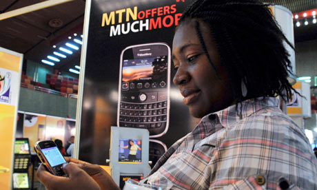 A delegate checks a BlackBerry at an exhibition during the West & Central Africa Com conference