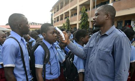 Nigeria teacher checks temperature