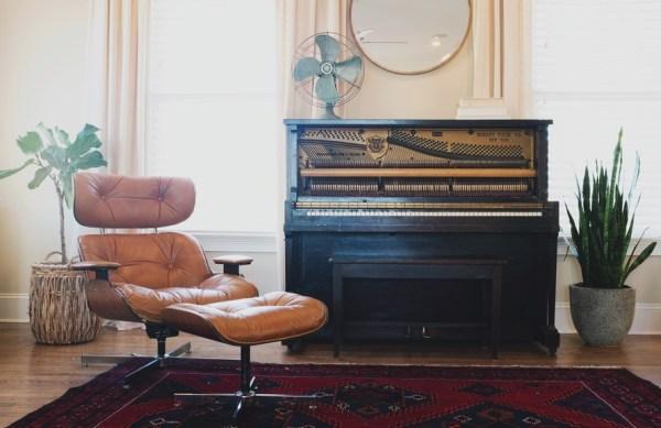 Black Upright Piano Near Orange Glider Chair