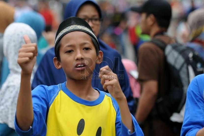 Salah seorang santri Tahfiz Al Quran Kauny yang ikut serta membaca Al-Quran saat Hari Bebas Kendaraan Bermotor di Jakarta, Ahad (30/11).  (Republika/Agung Supriyanto)
