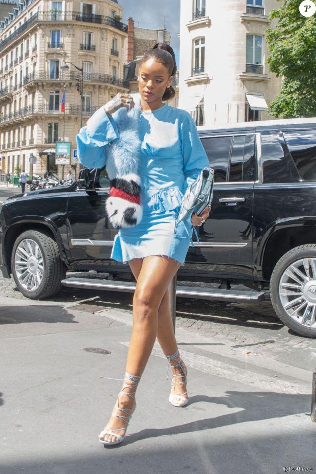 Rihanna arrive à la boutique Christian Dior sur l'avenue Montaigne, habillée d'une robe Marques Almeida (collection automne-hiver 2016) et de sandales Dsquared² (modèle RiRi). Une écharpe en fourrure Fendi et un sac Christian Dior complètent sa tenue. Le 29 juillet 2016.
