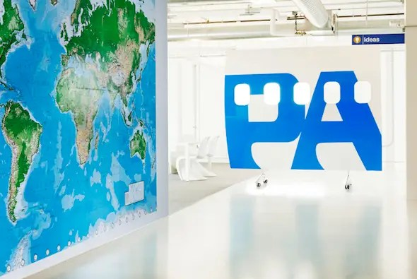 Travel is another big theme in Airbnb's office. A big Pan Am logo is plastered on the wall with a map of the world and airplane windows tinted on the glass.