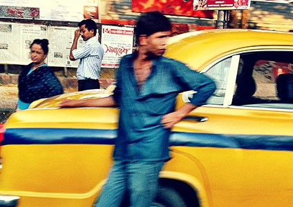 Blurred street scene showing yellow Kolkata taxi and people walking on the street