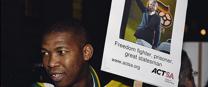 A man holds a poster with image of Nelson Mandela
