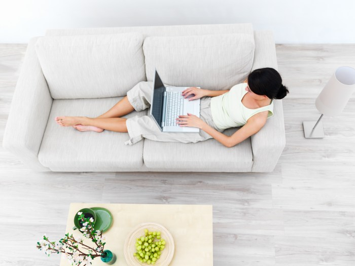 Modern Young woman sitting on sofa, working on laptop
