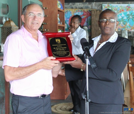 Former SLOC president Richard Peterkin receives plaque of appreciation from his successor Fortuna Belrose. Minister of Sports Shawn Edward was also in attendance.