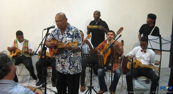 The late Frank Norville accompanied by a group of musicians performing  at a music and poetry fiesta put on by the Folk Research Centre and  Alliance Francaise.