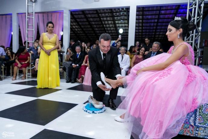 pai trocando o sapatinho da debutante