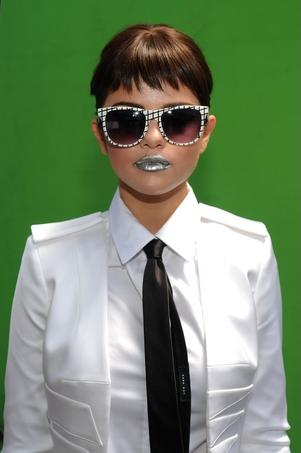 The video for Love You Like a Love Song features Selena Gomez with short hair, wearing a black tie and a white jacket with shoulder boards.