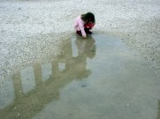 Girl plays in puddle reflecting The Acropolis