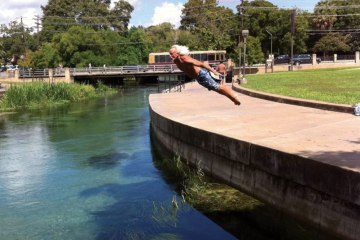The Sun God of Texas State diving into a river