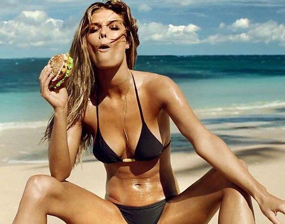 girl on beach eating a burger
