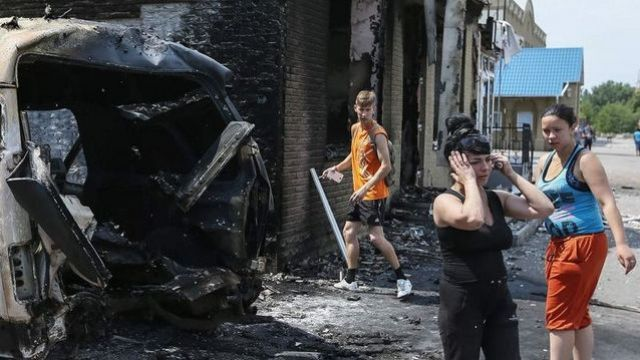 Local residents react near destroyed houses and vehicles after what locals say was overnight shelling by Ukrainian forces, in Slaviansk