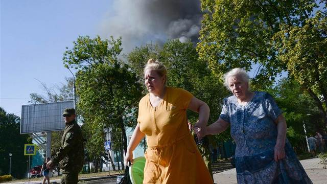 Women run from shelling in Donetsk, Ukraine. (AP Photo/Mstislav Chernov)
