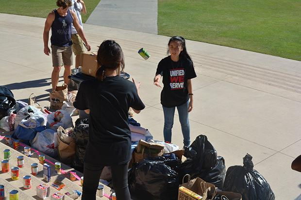 Biology majors, Gloria Yun (Left), 19, and Catherine Han (Right), 19, work diligently to display the items collected during the annual clothing and food drive. Photo credit: John Saringo-Rodriguez / Photo Editor