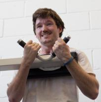 Stelmach smiles as he works out on an abdominal crunch machine in the Brown Center of Achievement. Stelmach said he works to make his body stronger instead of letting it succumb to his brain injury. Photo credit: Trevor Stamp / Daily Sundial