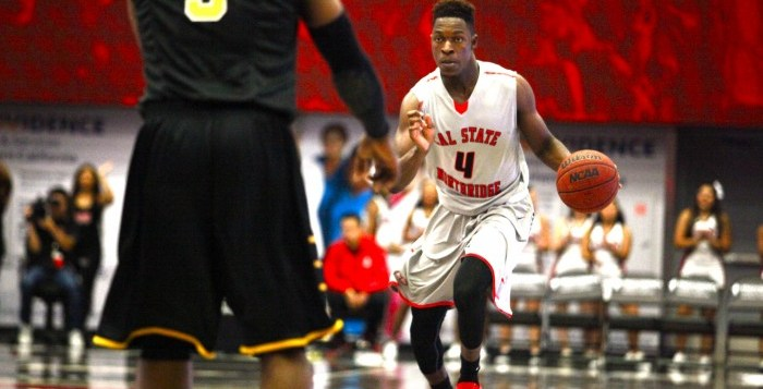 Freshman forward Tavrion Dawson (number 4) tries to run past opponent from Cal State L.A. (number 5).