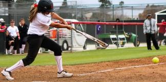 Softball athlete bats at home plate