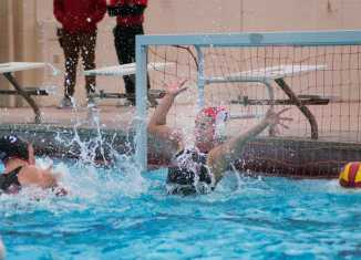 Student water polo athlete defends goal attempt from opposing athlete