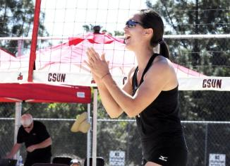 CSUN volleyball player claps in front of net