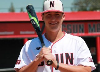 CSUN baseball athlete carries baseball bat while smiling