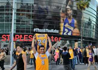 Man poses with Kobe Bryant jersey while wearing a Lakers jersey
