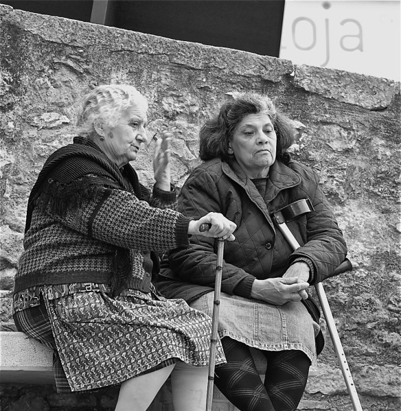 Two older Portuguese women sitting and talking in front of stone wall