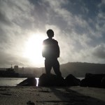 man-silhouette-on-rocky-beach-against-sun