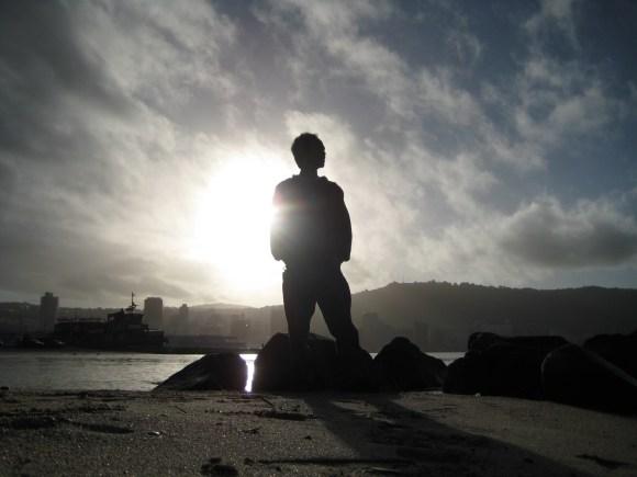 man-silhouette-on-rocky-beach-against-sun
