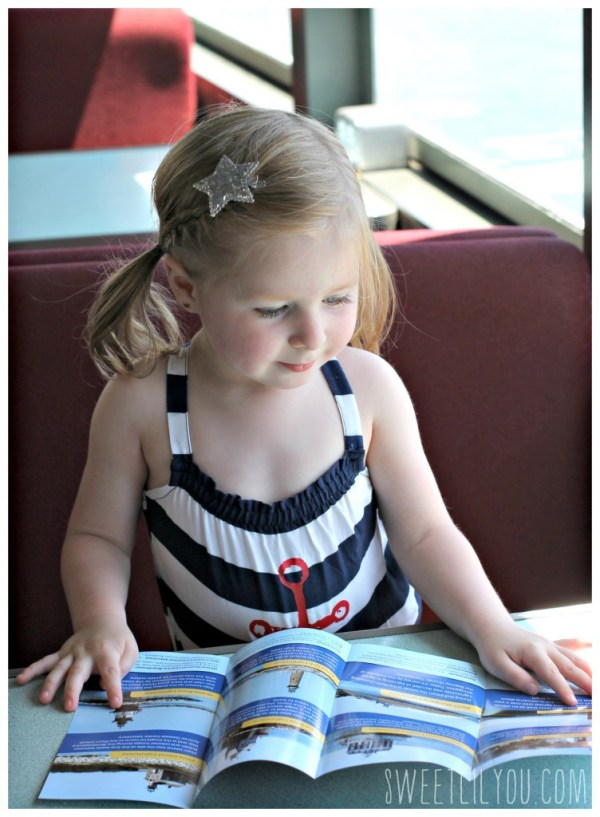 Avery reading the lighthouse cruise brochure