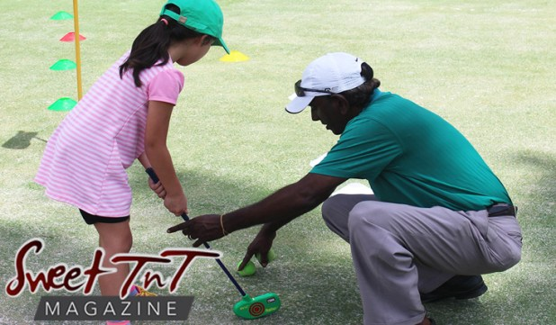 Girl in pink dress, pink shoes, green hat, green golf putter, learns to play golf at St Andrew's Maraval with coach man wearing green t shirt khaki pants, white hat stooping teaching on green golf course in Sweet T&T, Sweet TnT Magazine, Trinidad and Tobago, Trini, vacation, travel