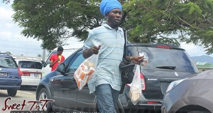 Nuts vendor selling salt, fresh, roasted peanuts on the streets in between vehicles at red traffic light on highway in sweet T&T for Sweet TnT Magazine, Culturama Publishing Company, for news in Trinidad, in Port of Spain, Trinidad and Tobago, with positive how to photography.