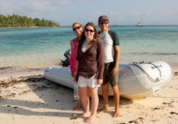 Karen, Edel, and Frank in front of dinghy with Tahina in background - West Holandes Cays, San Blas