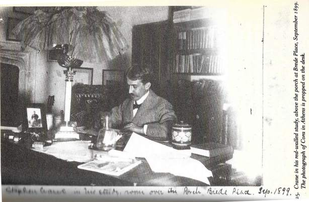 Benfey's caption: Crane in his red-walled study, above the porch at Brede Place, September 1899, The photograph of Cora in Athens is propped on the desk (The Double Life of Stephen Crane)