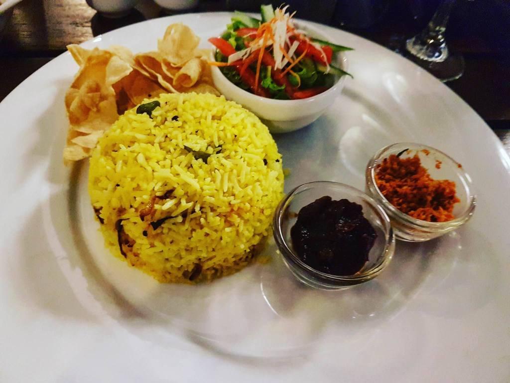 Curry Fish z szafranowym ryżem, pomidorowym chutney, chili, sałatką i chipsami papadam w restauracji SUGAR w Colombo