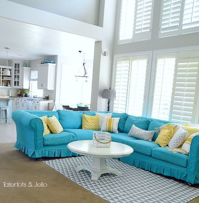 turquoise slipcover and yelllow and grey pillows