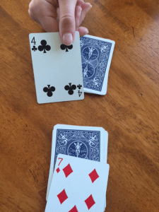 picture of hand flipping over a card from a deck of cards