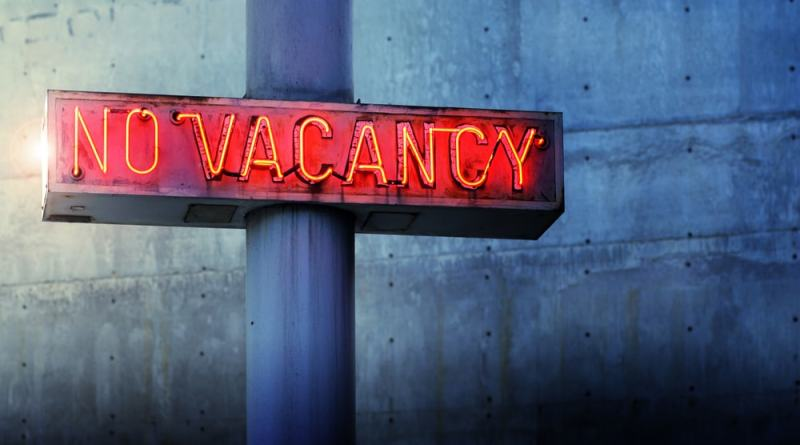 shutterstock_151308128 Glowing retro neon 'no vacancy' sign against cool blue wall background