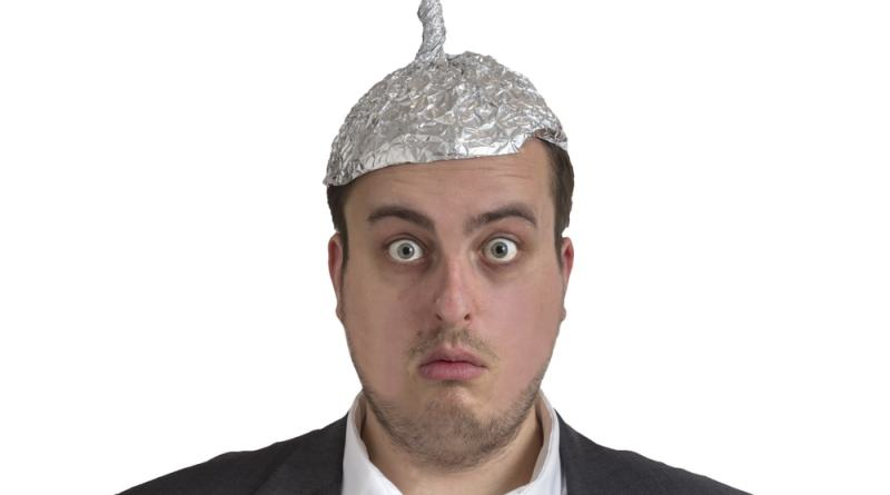 shutterstock_241641217 distraught looking conspiracy believer in suit with aluminum foil head isolated on white background