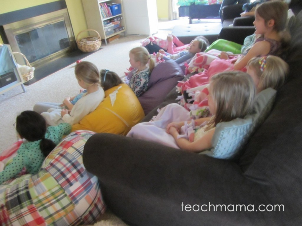 girls at frozen party cozy with blankets, watching movie