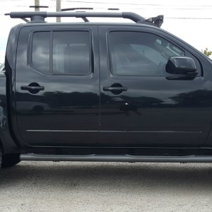 2016 Nissan Frontier PRO-4X with Westin grille guard, Retrax One MX bed cover, roof rack light bar